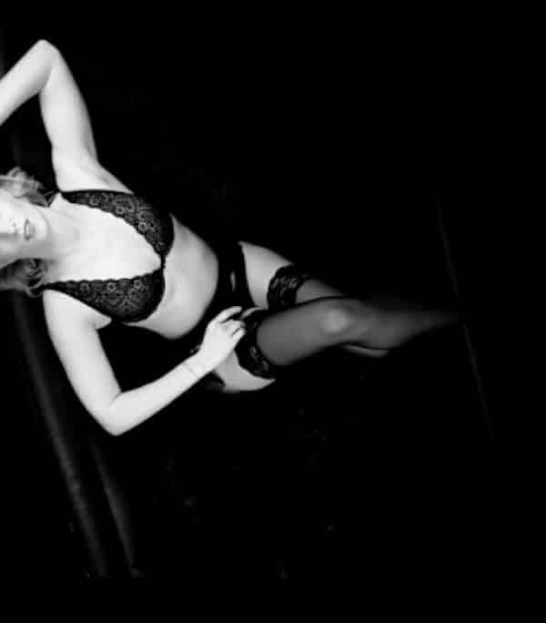 Larissa - Blondes Escort Bonn in schwarzen Dessous auf einem Sofa liegend.