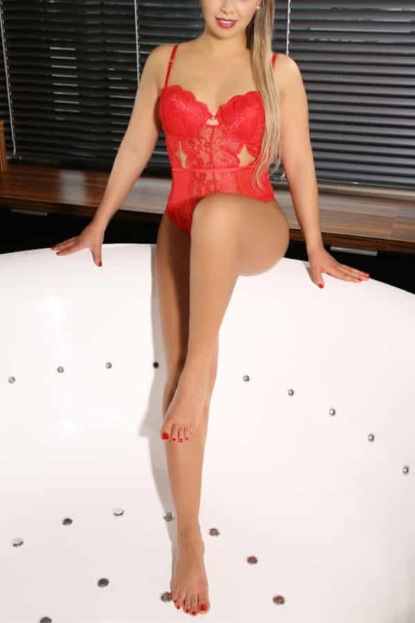 Lena - Escortmodel Dortmund im roten Body auf der Badewanne.