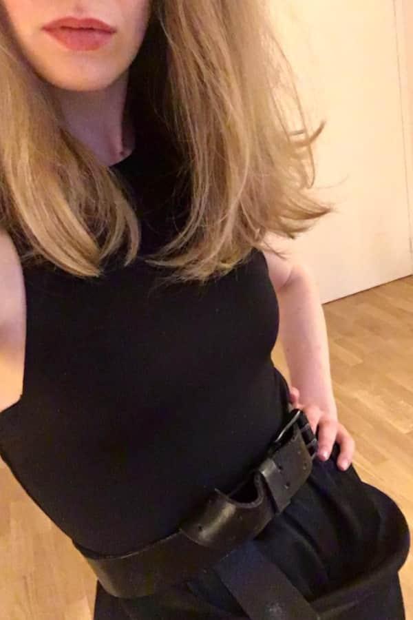 Ella - Elite Escort Berlin im schwarzen Kleid mit offenem Haar und roten Lippen.