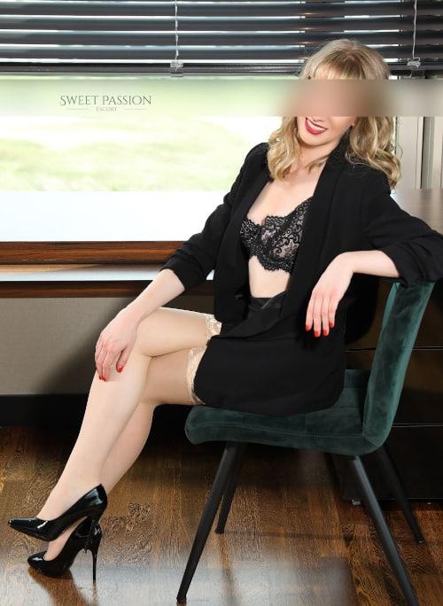 Ella - Elite Escort Berlin im Business Outfit mit schwarzem Rock und schwarzen High Heels.