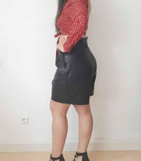 Jessica - High Class Escortdame Frankfurt von der Seite im Lederrock mit High Heels.