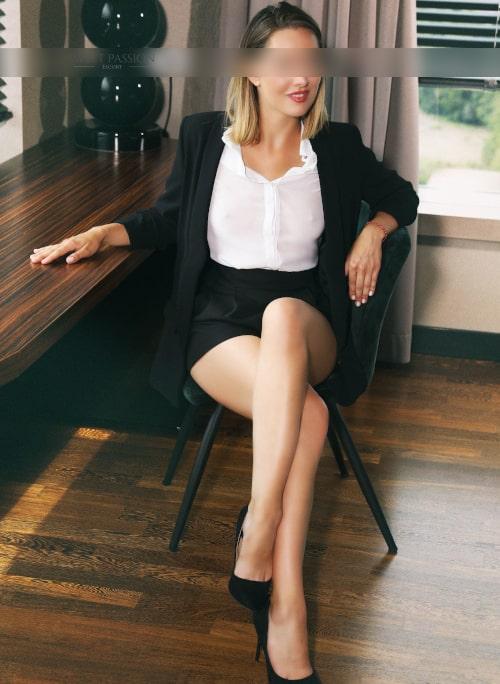 Jolie - High Class Escort Köln im Business Outfit am Schreibtisch.