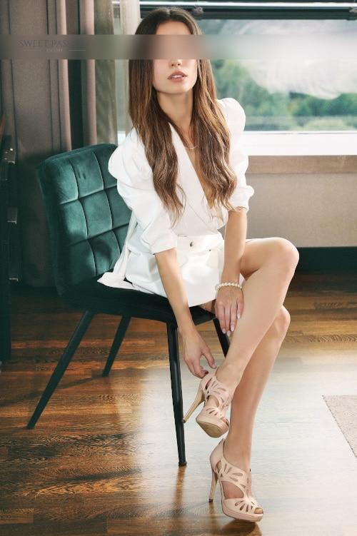 Laureen - Escortdame Bielefeld sitzen dauf einem Stuhl mit langem Haar und offenen Lippen.