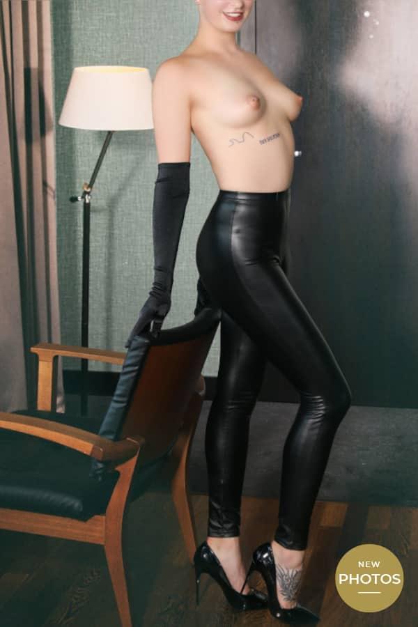 Amelie - Escortlady NRW in schwarzer Lederhose und Handschuhen.