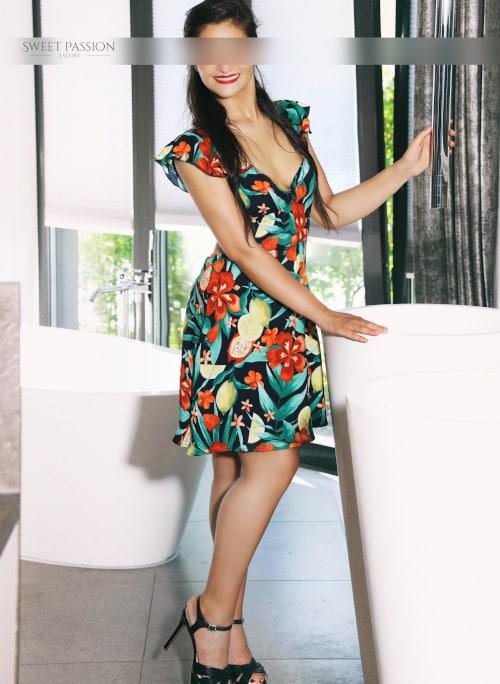 Jessica - High Class Escortdame Deutschland im geblümten Kleid mit High Heels.