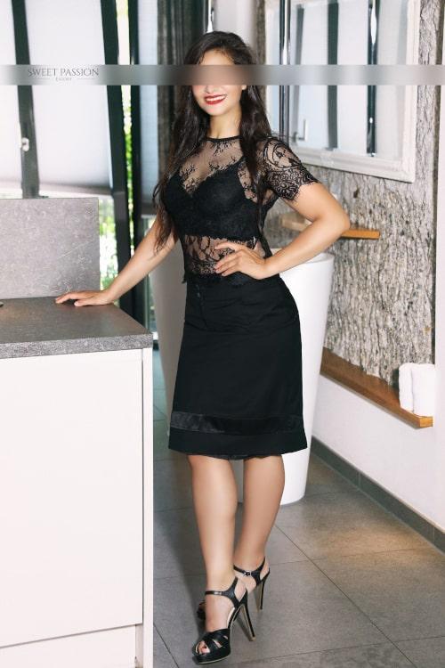 Jessica - High Class Escortdame Frankfurt in High Heels mit einem schwarzen Kleid aus Spitze.