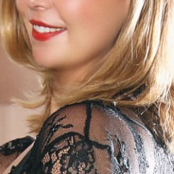 Kira - Escort Düsseldorf mit einem breiten Lächeln und roten Lippen.