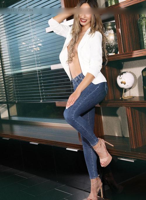 Bestaunen Sie die Kölner Escortdame Bella in Jeans und hohen Sandalen.