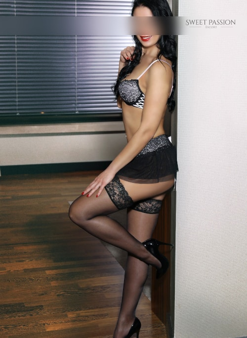 NRW Escort Elaine in Dessous mit Rock und High Heels.