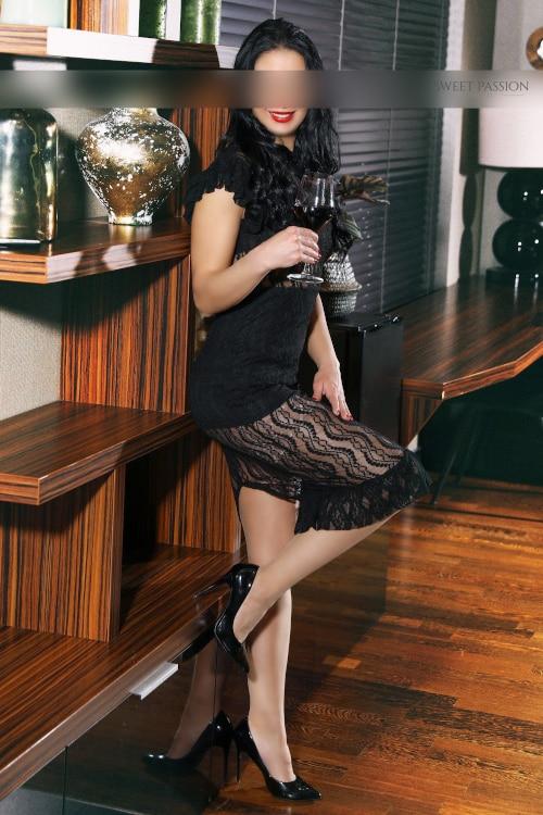 Escortmodel Elaine aus Köln im schwarzen Kleid mit einem Glas Rotwein in der Hand.
