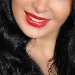 Elite Escort Köln Elaine mit einem breiten Lächeln und roten Lippen.