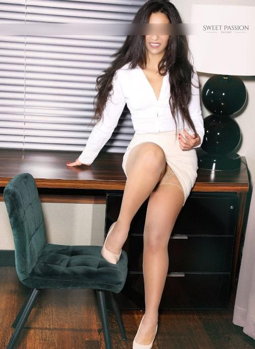 Business Escortdame Jana in einer weissen Bluse und halterlosen Strümpfen.