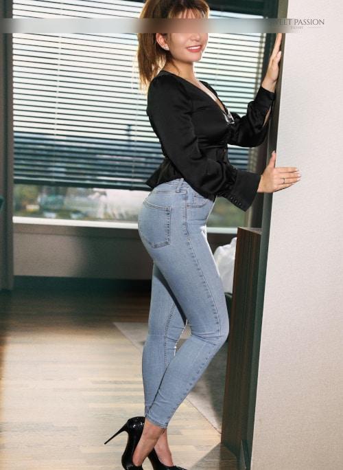 Escortmodel Lucy aus Frankfurt in Jeans und schwarzer Bluse im Türrahmen.