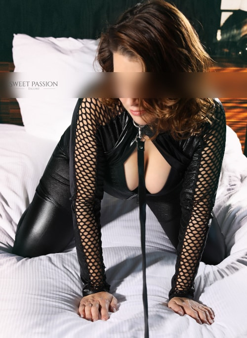 Nike - BDSM Escortdame Neuss im Lederanzug auf dem Bett.