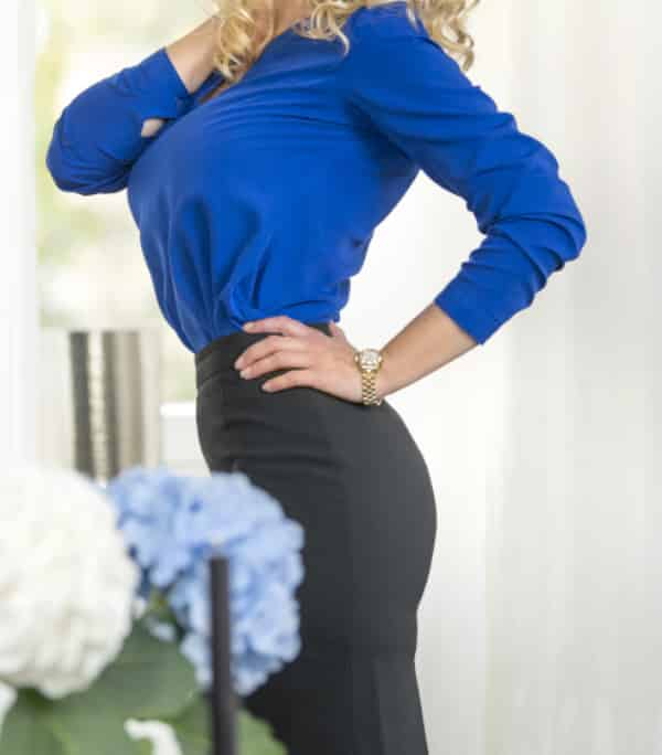 Angelina - Escort Model Dortmund im blauen Business Outfit hinter einem Blumenstrauss