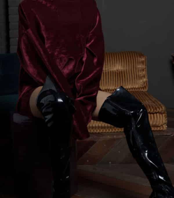 Chloe - Elite Escort Berlin im roten Pullover mit schwarzen Lederstiefeln
