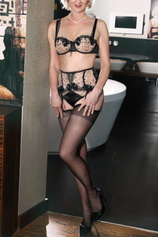Clea - Escortdame aus Köln in transparenten schwarzen Dessous im Eingang eines Badezimmers.