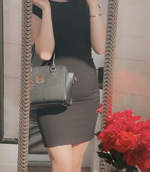 Naomi - VIP Escortdame Bielefeld mit schwarzen Businesskleid mit einer schwarzen Handtasche.