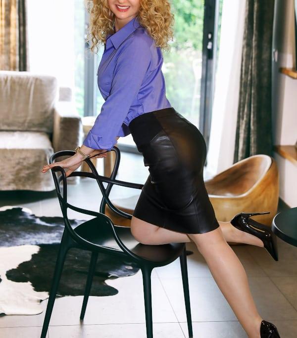 Angelina - Blondes Escort Dortmund im Business Outfit auf einem Stuhl knieend.