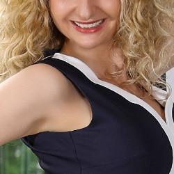 Angelina - Blondes Escort Dortmund mit blonden Locken und einem breiten Lächeln.