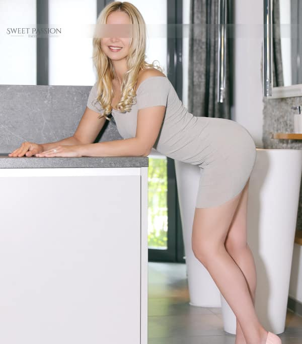 Ava - Blonde Escortdame München im engen Kleid über eine Theke gelehnt.