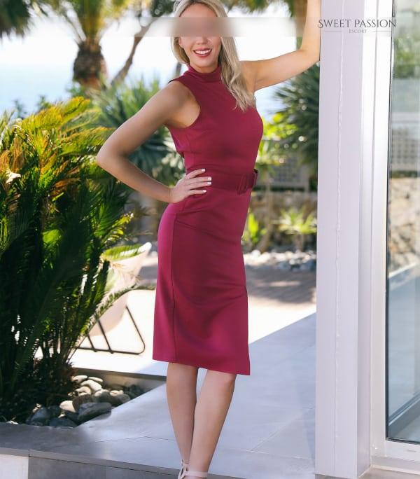 Celine - Escort Agentur Frankfurt Model im roten Kleid auf einer Terasse vor Palmen.