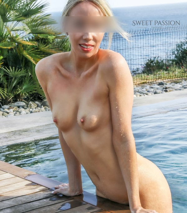 Celine - Escort Dame Frankfurt nackt im Swimmingpool vor dem Meer.