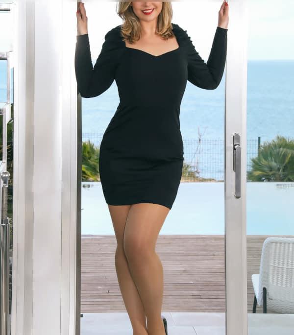 Kira - Blondes Escort Düsseldorf im schwarzen Kleid mit schwarzen High Heels vor der offenen Terassentür.