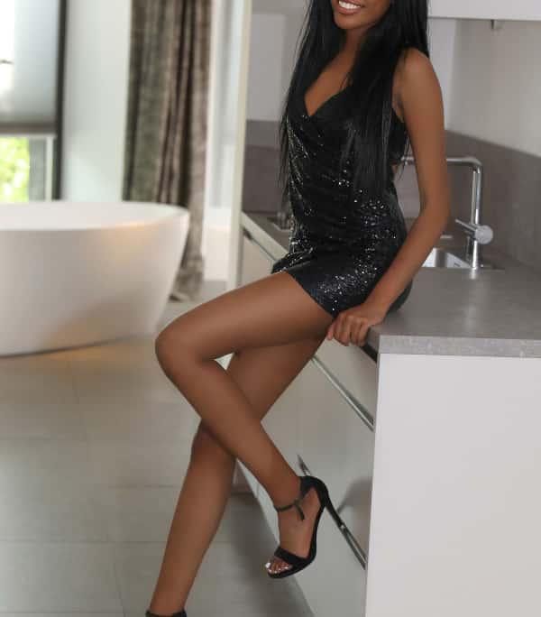 Emy - schwarze Escortdame Frankfurt in kurzen schwarzen Kleid an einer Kommode gelehnt.