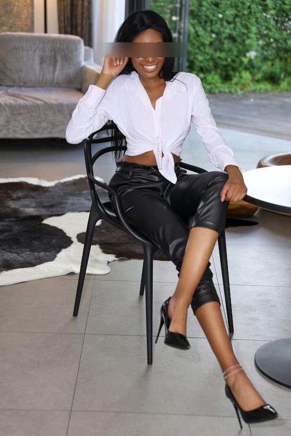 Emy - schwarze Escortdame Frankfurt im Business Outfit auf einem Stuhl sitzend.