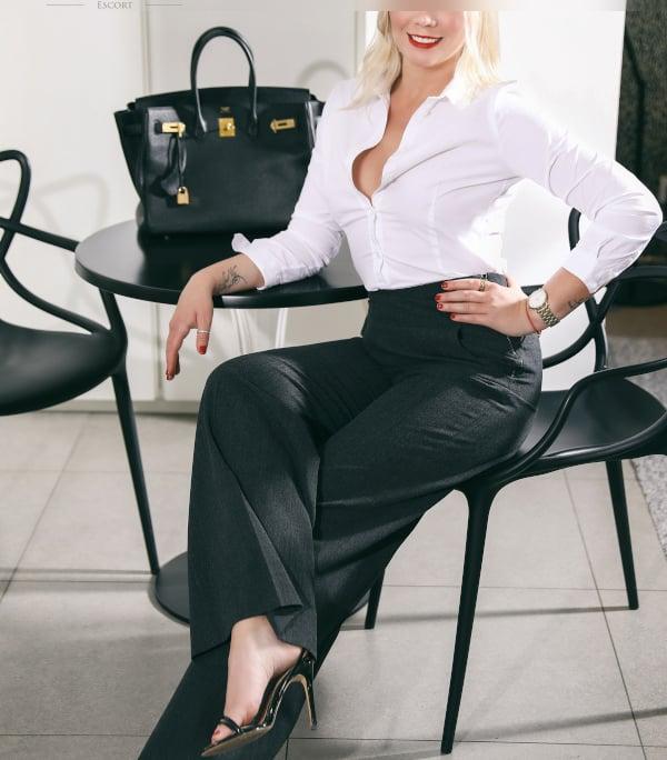 Franziska - Elite Escortdame Düsseldorf im BUsiness Outfit auf einem Stuhl sitzend.