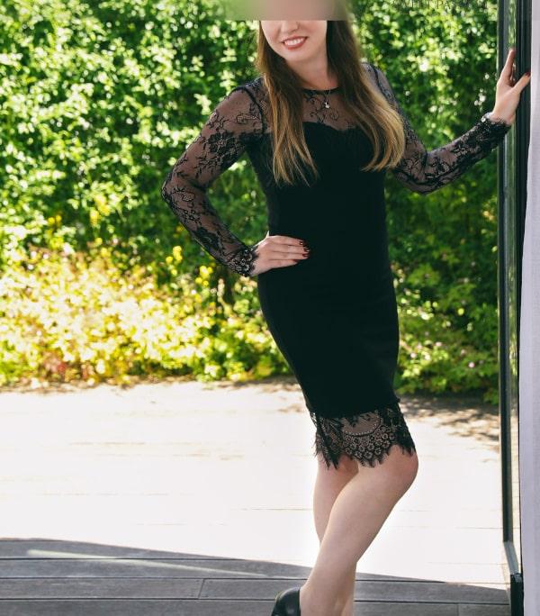 Sophia- VIP Escortmodel Berlin an der offenen Terassentür im schwarzen Kleid mit Spitze.