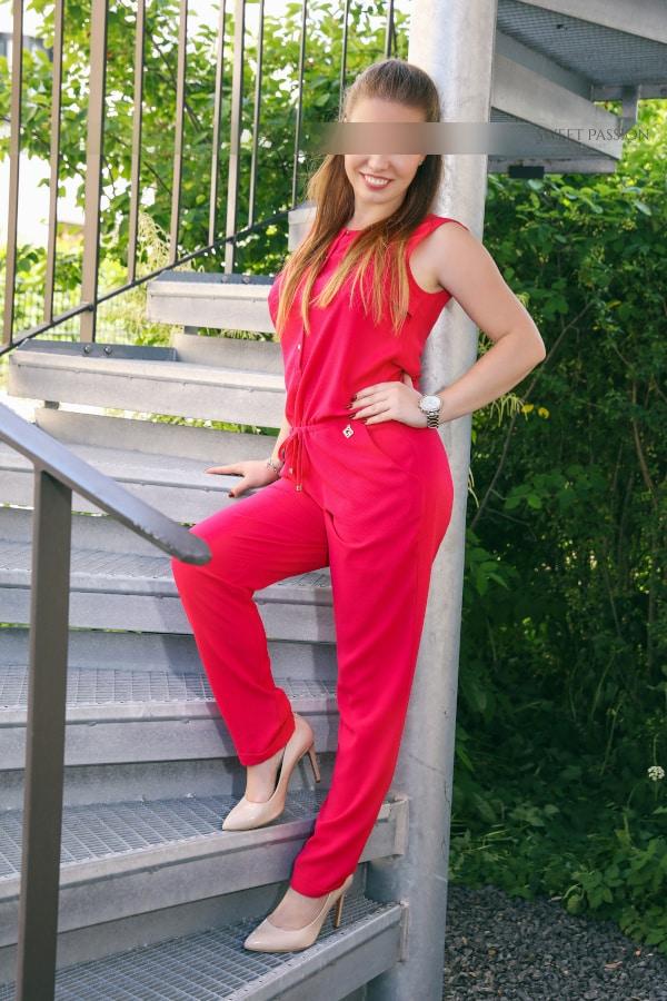 Sophia- VIP Escortmodel Berlin auf der Terasse im leuchtenden roten Jumpsuit.