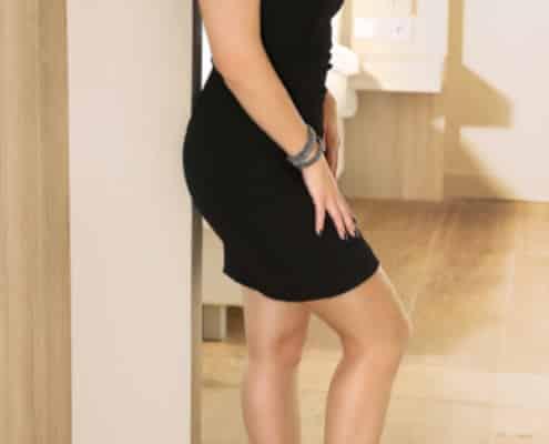 Katrina - Essener Escortlady im schwarzen Kleid in einem Türrahmen an die Wand gelehnt.