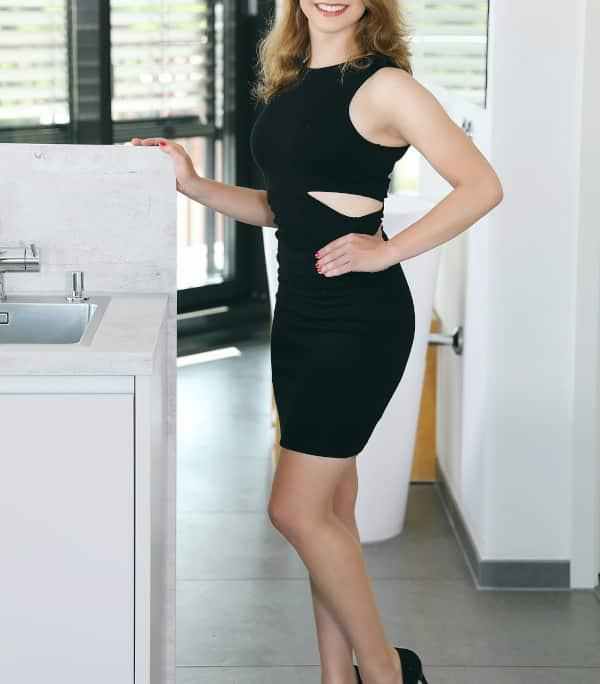 Zoe - Blondes Escort Hamburg im schwarzen engen Kleid mit schwarzen High Heels.
