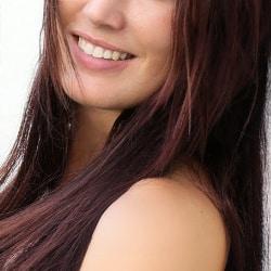 Lara - Escortdame Hamburg mit einem breiten Lächeln und offenem Haar.