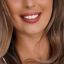 Liana -Escortdame Köln mit lockigem Haar und einem breiten Lächeln.