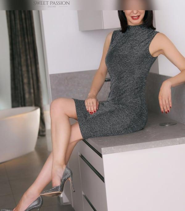 Madeleine - Reifes Escort Braunschweig im grauen Kleid auf einer Kommode sitzend.