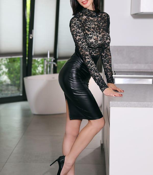 Madeleine - Reifes Escort Braunschweig im Lederrock und schwarzen High Heels an einer Kommode stehend.