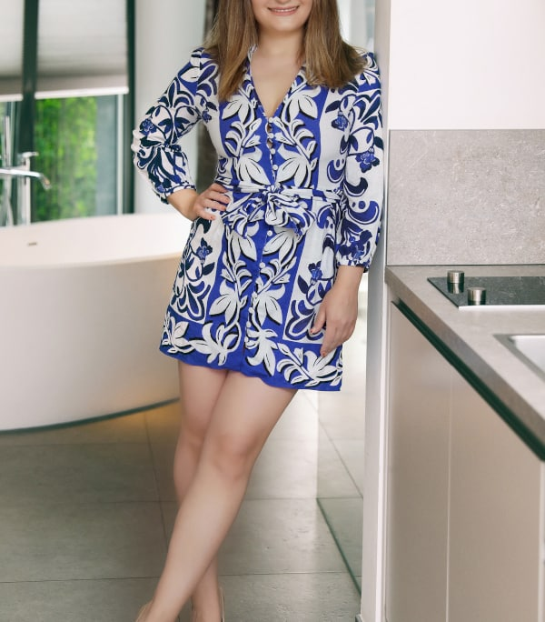 Sarah - Escort aus Düsseldorf in einem blauen Sommerkleid an einer Wand lehnend.