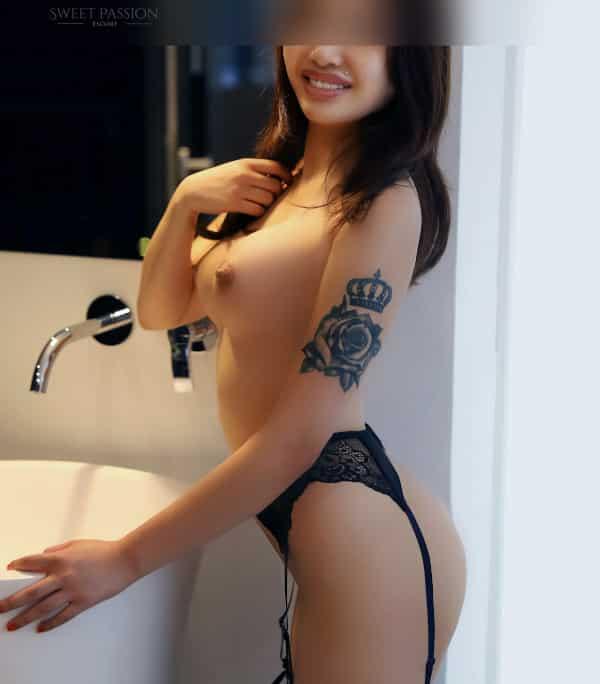 Adriana - Asiatisches Escort Köln im schwarzen Strapshalter an einem Waschbecken stehend.