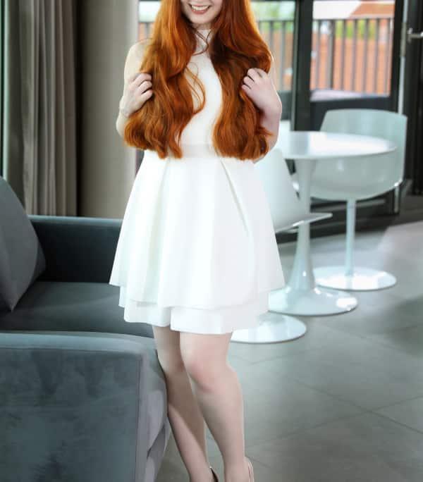 Amalia - Junge Escortdame Frankfurt im weissen Kleid vor einem Sofa stehend.