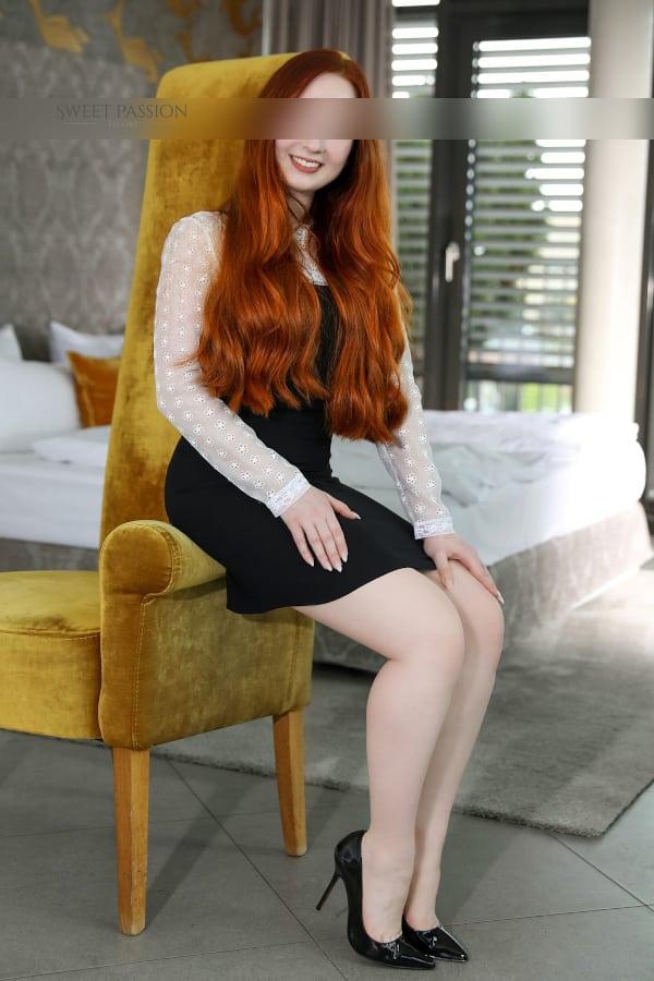 Amalia - Junge Escortdame Frankfurt im schwarzen Kleid und schwarzen High Heels auf der Lehne eines Sessels sitzend.