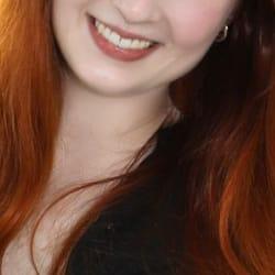Amalia - Junge Escortdame Frankfurt mit offenem roten Haar und einem breiten Lächeln.