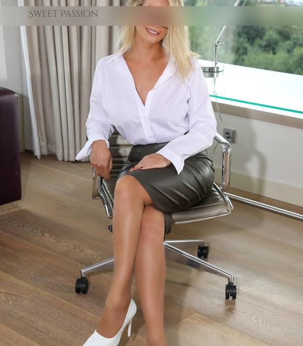 Diandra - Reifes Escort Bremen im Business Outfit auf einem Stuhl sitzend.
