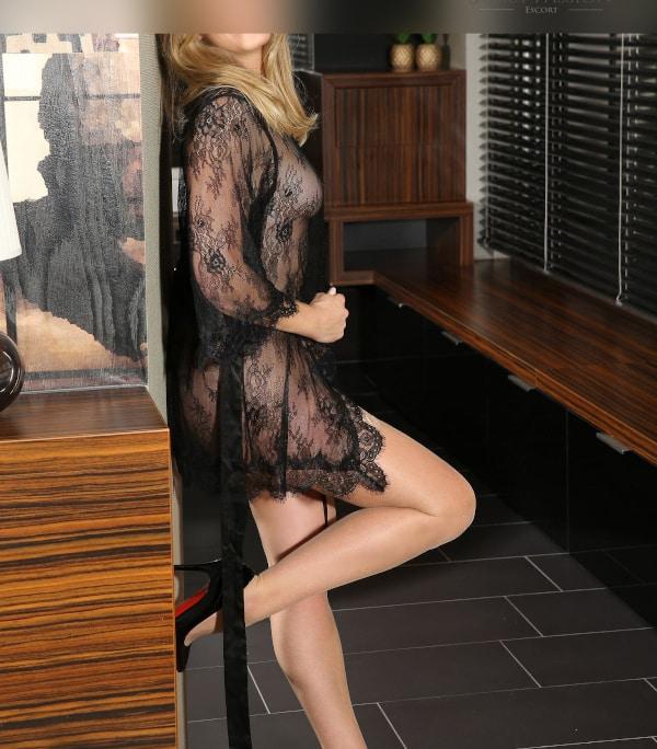 Escort Lady Düsseldorf Klara im durchsichtigen Kimono mit einem Bein an der Wand stehend.
