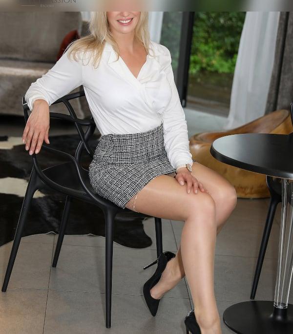 Larissa - Kurviges Escort Köln in Business Outfit auf einem Stuhl sitzend.
