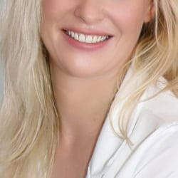 Larissa - Kurviges Escort Köln mit einem breiten Lächeln und offenem blondem Haar.