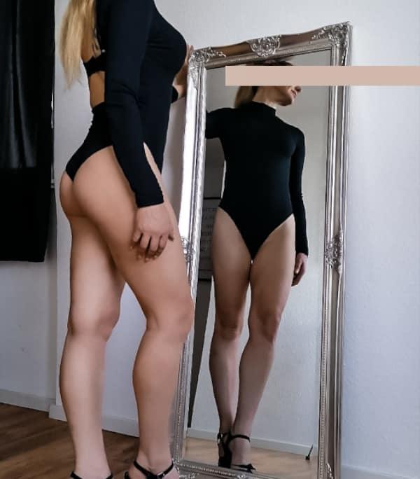 Valentina - Blondes Escort Köln im schwarzen Body mit High Heels vor einem Spiegel stehend.